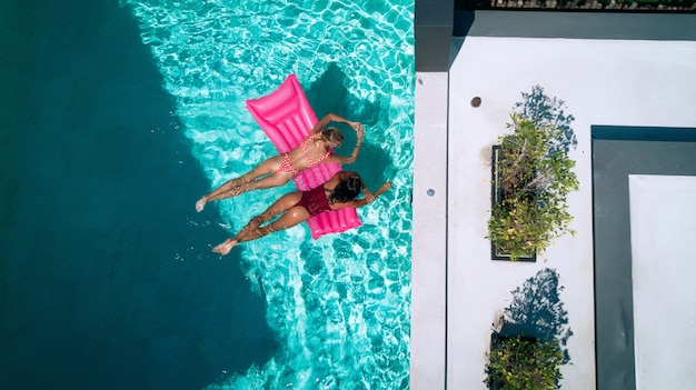 Antenne twee vrolijke jonge vrouwen die genieten op opblaasbare floaties die in pool babbelen