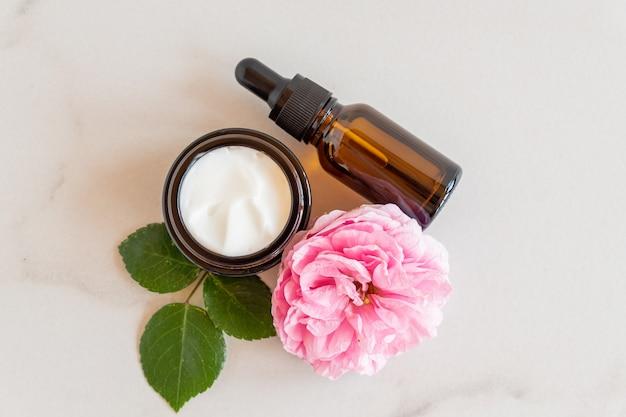 Anti-aging collageen gezichtsserum in donkere glazen fles en gezichtscrème op marmeren achtergrond met groene bladeren en roze bloem. natuurlijk organisch cosmetisch schoonheidsconcept.