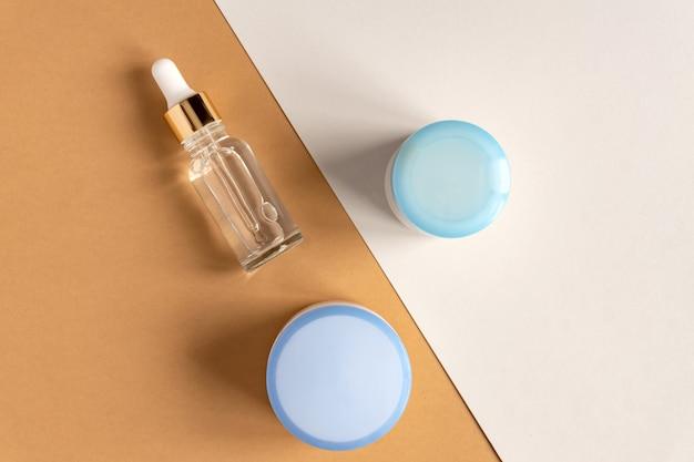 Anti-aging collageen gezichtsserum in doorzichtige glazen fles met gouden pipet en gezichtscrème op dubbele beige en grijze achtergrond.