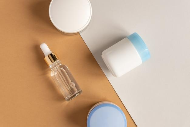 Anti-aging collageen gezichtsserum in doorzichtige glazen fles met gouden pipet en gezichtscrème op dubbele beige en grijze wand. natuurlijk organisch cosmetisch schoonheidsconcept.