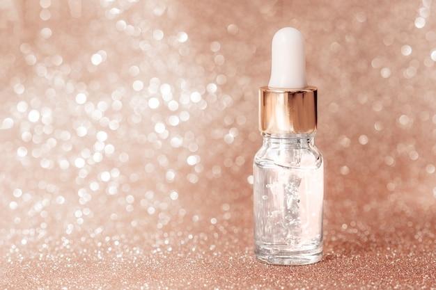 Anti-aging serum met collageen en peptiden in glazen fles met druppelaar op goud