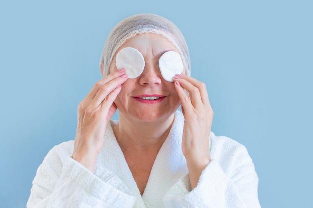Anti leeftijd concept. gelukkige natuurlijke vrouw seniora met een wattenschijfje reinigt de huid. natuurlijke spa-behandelingen thuis, biologische cosmetica. gezondheidszorg en cosmetologie, volwassen mensen, nieuwe senior