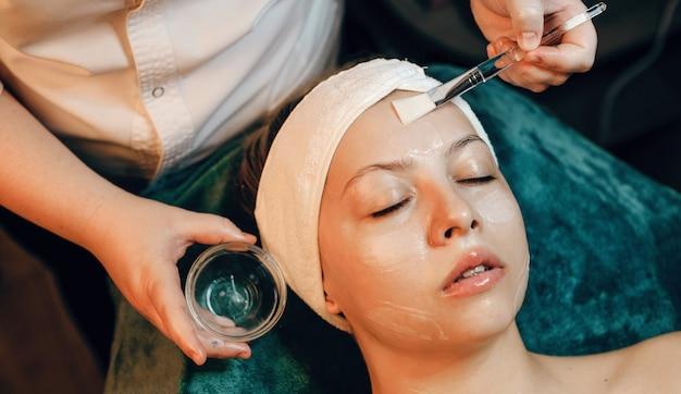 Anti-veroudering gezichtsmasker toegepast op een blanke vrouw in een wellness-kuuroord met een speciale borstel