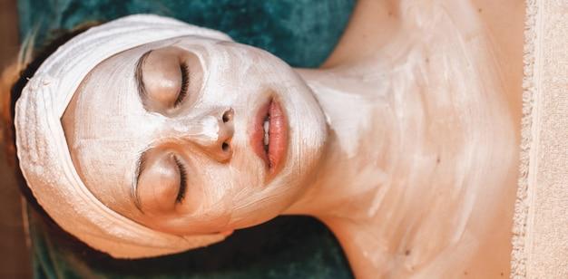 Anti-verouderingscrème aangebracht op het gezicht van de klant tijdens een spa-procedure in het wellnesscentrum