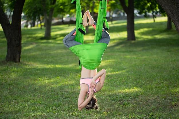 Anti-zwaartekracht yoga, vrouw doet yoga oefeningen in het park