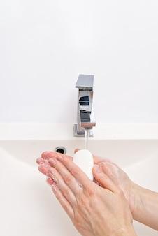 Antibacteriële zeep in de handen. zeepachtige handen. was uw handen met water en zeep.
