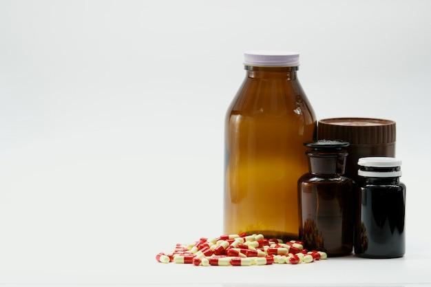 Antibiotische capsulepillen met de lege fles van het etiket amberglas op witte achtergrond met exemplaarruimte. farmaceutische industrie. apotheek achtergrond. antimicrobiële resistentie tegen geneesmiddelen. wereldwijde gezondheidszorg.