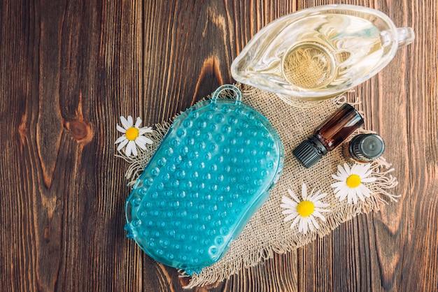 Anticellulite siliconen massager voor lichaam met oliën en kamilles op donker hout