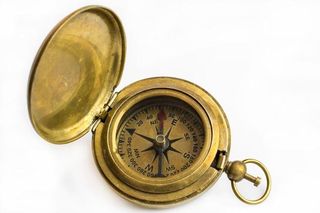 Antiek bronzen kompas close-up geïsoleerd op een witte achtergrond.