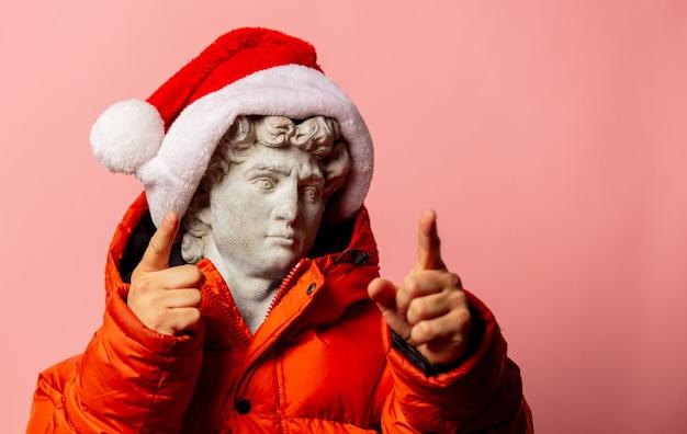 Antiek standbeeld gekleed in donsjack en santa claus-hoed op roze muur