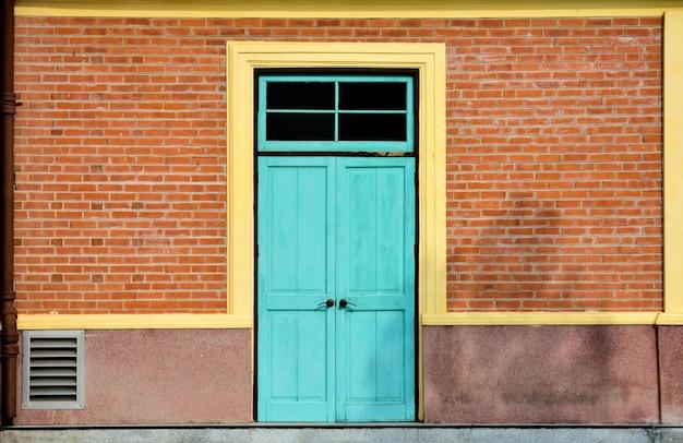 Antieke blauwe houten deur bij de rode baksteenbouw