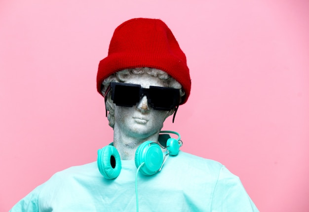 Antieke buste van man in hoed met hoofdtelefoons en zonnebril
