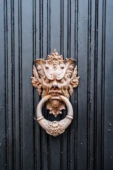 Antieke deurklink in de vorm van een demonische afbeelding met een ring in de mond in vergulding