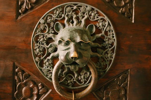 Antieke deurklink op een houten deur met patronen in de vorm van het gezicht van een mythisch personage