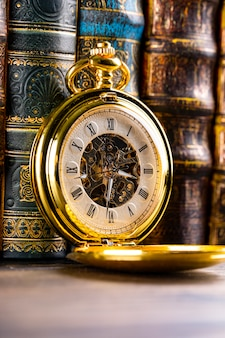 Antieke klok op de achtergrond van vintage boeken. mechanisch uurwerk aan een ketting.
