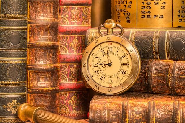 Antieke klok op de achtergrond van vintage boeken.
