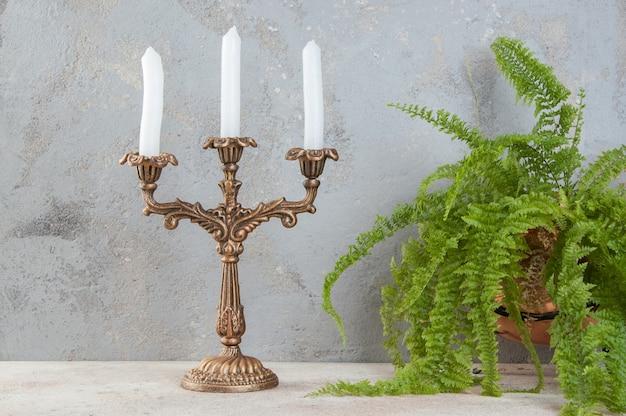 Antieke koperen kandelaar voor drie kaarsen op betonnen ondergrond. ruimte voor tekst kopiëren.