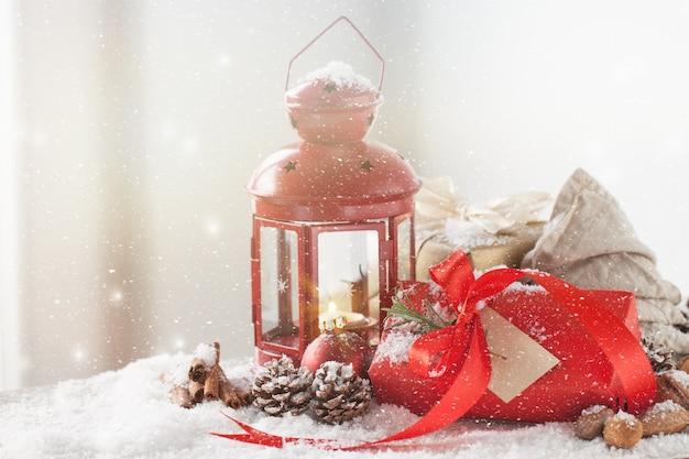 Antieke lamp met een rode gift terwijl het sneeuwt
