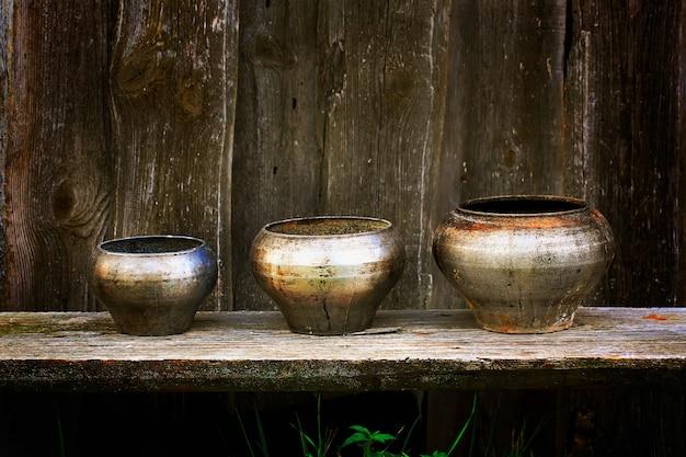 Antieke potten voor het koken in de russische oven donkere houten achtergrond rustieke stijl retro wijnoogst