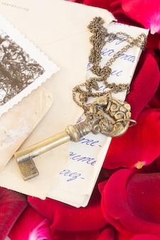 Antieke sleutel met oud papier en karmozijnrode rozenblaadjes als symbool van liefde