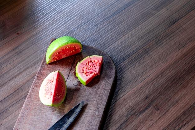 Antieke stalen mes en gesneden rode guaves op rustieke houten tafel