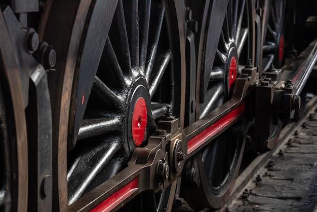 Antieke treinwielen op de rails in rood en zwart