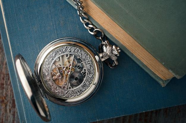Antieke vintage klok op oude boeken. schakelt mechanische horloges in