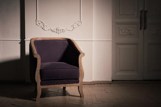 Antieke violet eiken fauteuil in het donkere interieur