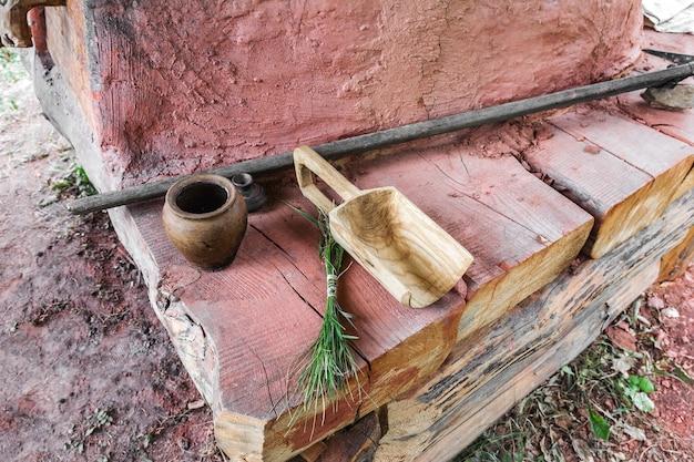 Antieke voorwerpen van landelijk gebruik huishoudelijk gebruiksvoorwerpen liggen op houten planken bij de kleikachel