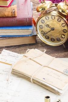 Antieke wekker met stapel post en boeken