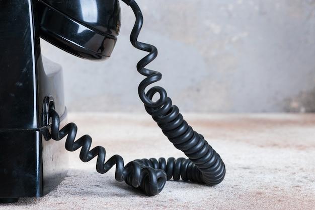 Antieke zwarte roterende telefoon op concrete achtergrond.