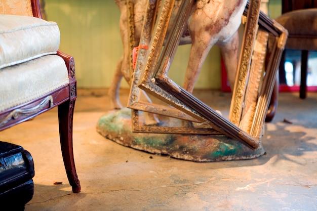 Antiekwinkelscene met stoelpoot en frames