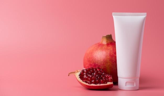 Antioxidant bad advertentie levensstijl verwennerij concept. panoramische foto van een potcontainer met stijlvolle pakketcrème met voedingsmineralen, rode granaatappelaroma, geïsoleerde pastelkleurige achtergrond