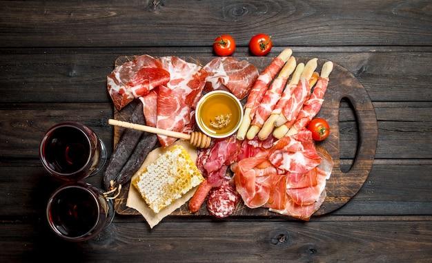 Antipasto achtergrond. diverse assortiment van vlees snacks met rode wijn. op een houten achtergrond.