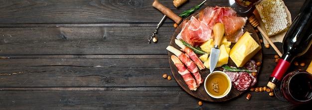 Antipasto achtergrond. diverse vlees en kaas snacks met rode wijn.