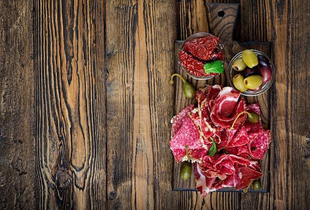 Antipasto-cateringsschotel met spek, schokkerig, worst en olijven op een houten achtergrond.