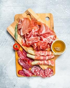 Antipasto. de verschillende soorten vlees. op een rustieke ondergrond.