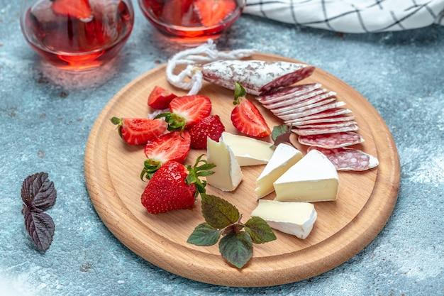 Antipasto gesneden spaanse fuet salami wurst, camembert kaas, aardbeien en glas rose wijn op blauwe achtergrond. voedsel recept achtergrond. detailopname.