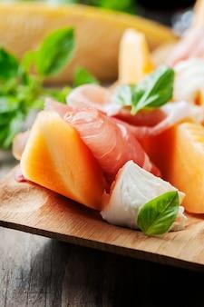 Antipasto met meloen, mozzarella, ham en basilicum