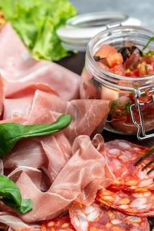 Antipasto schotel koud vlees bord met prosciutto, plakjes ham, salami met basilicum, tomaten en olijvensalade. vlees voorgerecht. verticaal beeld. bovenaanzicht.