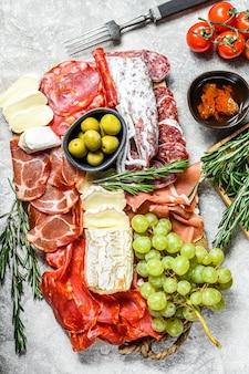 Antipasto schotel koud vlees met druiven, prosciutto, plakjes ham, beef jerky, chorizo salami, fuet, camembert en geitenkaas