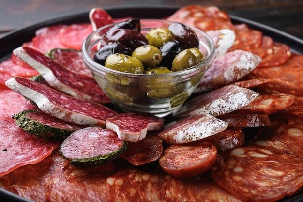 Antipastoschotel koud vlees met chorizo, fuet, salami, salchichon en longaniza op donker hout