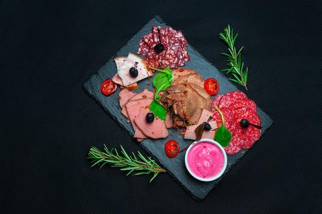Antipastoschotel koud vlees met prosciutto, worst, salami op leisteen stenen bord over marmeren achtergrond. vlees voorgerecht