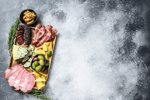 Antipastoschotel met ham, ham, salami, blauwe kaas, mozzarella en olijven. grijze achtergrond. bovenaanzicht. ruimte voor tekst