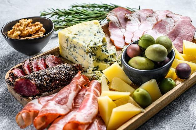 Antipastoschotel met ham, ham, salami, blauwe kaas, mozzarella en olijven. grijze achtergrond. bovenaanzicht