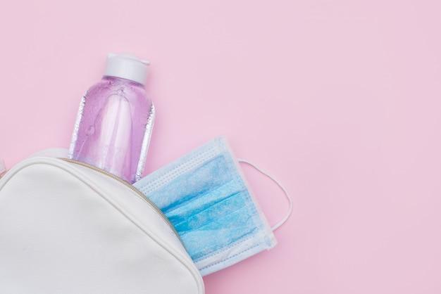 Antiseptische en steriele bescherming gezichtsmasker in witte handtas op roze tafel met een kopie ruimte.