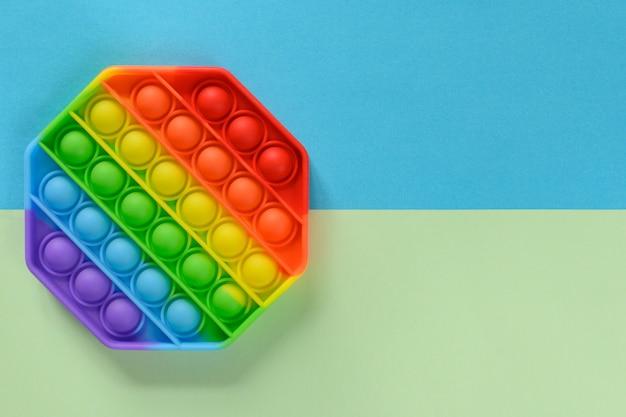 Antistress siliconen speelgoed popit op groene en blauwe achtergrond met kopieerruimte