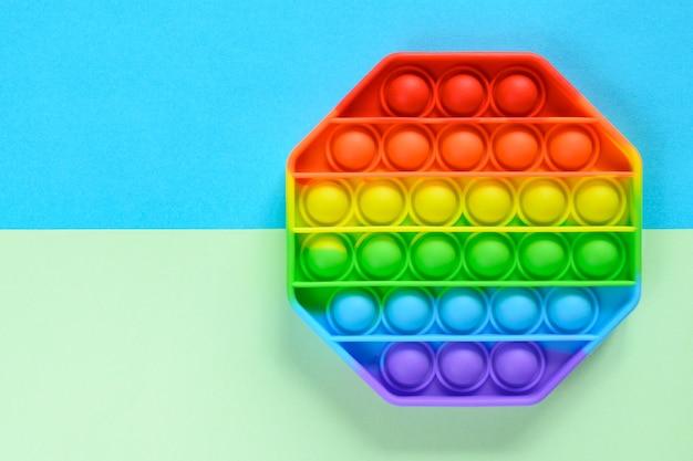 Antistress zintuiglijk speelgoed popit op groenblauwe achtergrond met kopieerruimte