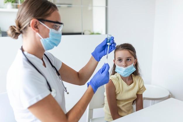 Antivirale immunisatie campagne concept. arts vaccineren meisje. meisje met medische maskers wordt ingeënt tegen covid-19, arts die een injectie met coronavirusvaccin geeft in het ziekenhuis.