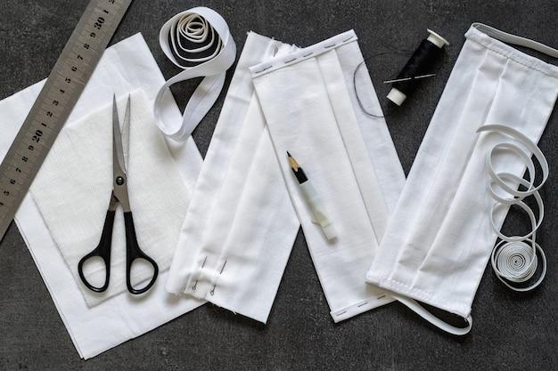 Antivirus bescherming. beschermende maskers naaien met zijn eigen handen gemaakt van zwarte stof. details en afgewerkt masker